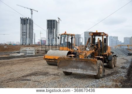 Motor Grader And Soil Compactor At A Construction Site Level The Ground And Gravel Stones For The Co