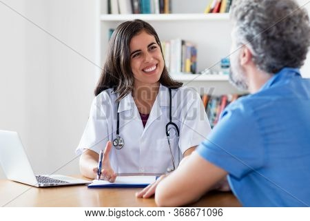 Laughing Mexican Female Doctor Talking With Patient At Hospital
