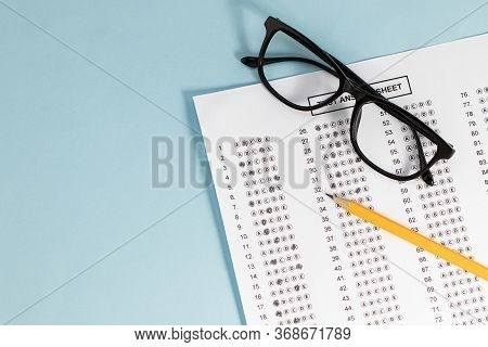 Take The Exam, Write The Exam. Exam Paper On Blue Background, Top View Copy Space
