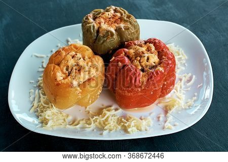 Stuffed Bell Peppers. Three Cooked Stuffed Peppers On A White Plate. Delicious Multi-colored Peppers