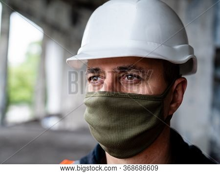 Close-up Of A Male Construction Worker In A Construction Helmet And Protective Medical Mask On A Con
