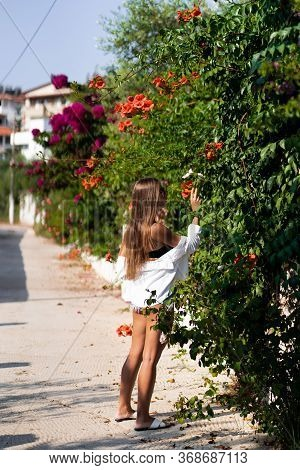 Beautiful Stylish Slim Girl Standing In Front Of Bush With Flowers. Girl Wears Short White Shirt , S