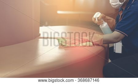 Woman Hand In Protective Orange Rubber Gloves Holding Green Microfiber Cleaning Cloth And Wiping Dus