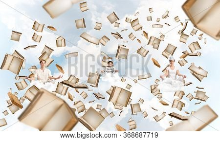 Young Family Keeping Eyes Closed And Looking Concentrated While Meditating Among Flying Books In The