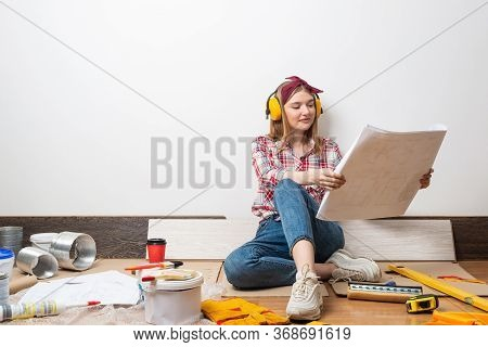 Beautiful Girl Sitting With Paper Blueprint In Hand. Home Remodeling And House Interior Redesign. Co