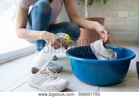 Closeup Of A Woman Spraying Disinfectant On Her Shoes Inside A Bucket After Getting Home From Outsid