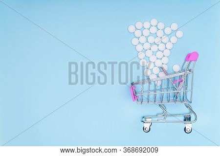 Consumers Basket On A Blue Medical Background In Which White Pills Fall. Concept Of Increasing Medic