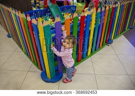 A Cute Little Baby Climbs At The Colorful Fence Of A Childrens Playroom, Looks In The Camera And Wan
