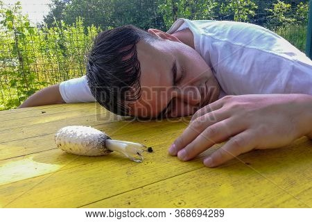 Oncpt Of Poisoning, On A Yellow Street Table Lies A Poisonous Mushroom And An Unconscious Adult Man