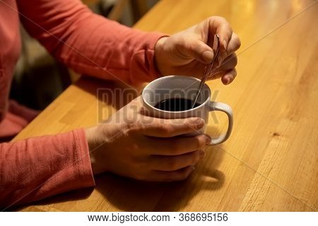 Close-up Female Hands Hold A White Cup With A Warm Drink And Mix With A Teaspoon On A Wooden Table.