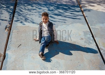 Funny Preschooler Boy (black, African-american) Playng At Urban Background. He Uses A Concrete Slab