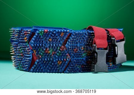 The Massage Belt Is Blue-red With Spikes, Metal Needles, Lying On The Arctic Surface And Green Backg