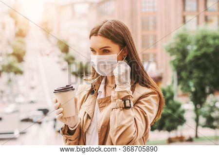 Stylish Woman In Medical Face Mask, Protective Gloves Drink Takeaway Coffee On City Street. Trendy H
