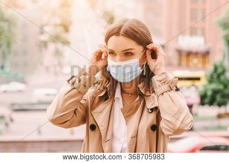 Beautiful Stylish Girl Wear Medical Face Mask On Sunny City Street. Young Elegant Happy Hipster Woma