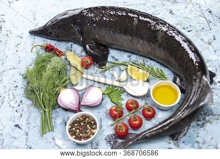Fresh Sturgeon Fish With Vegetables On Wooden Background