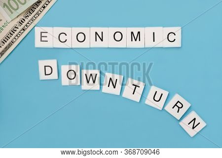 Phrase Economic Downturn Spelled Out In Wooden Letter Tiles On Trendy Blue Background. Economic And
