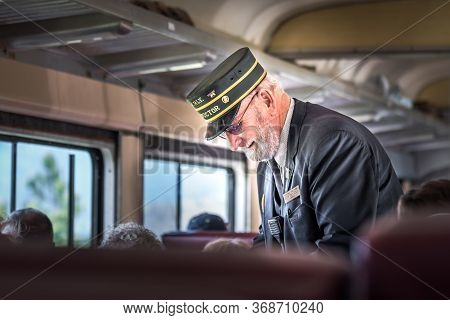 Summerland, British Columbia/canada - May 14, 2017: The Conductor Takes Tickets From Passengers On T