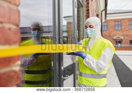 quarantine and pandemic concept - healthcare worker in protective gear or hazmat suit, medical mask, gloves and goggles enclosing building with caution tape outdoors
