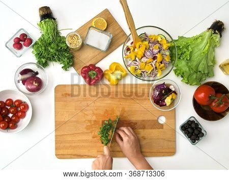 healthy eating, vegetarian food and cooking concept - POV shot of hands with knife chopping parsley on wooden cutting board for salad at kitchen
