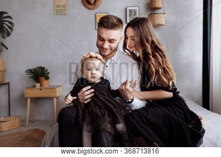 Mom, Dad And Little Girl Having Fun And Hugging At Home On Bed. Mothers, Fathers And Babys Day. Happ