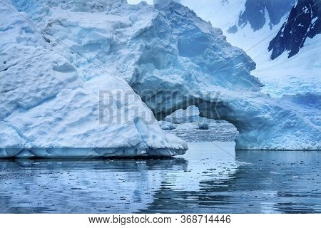 Snowing Floating Blue Iceberg Arch Reflection Paradise Bay Mountains Skintorp Cove Antarctica. Glaci