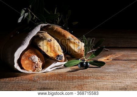Traditional Italian Puccia Breads With Black Olives In A Cotton Bag, Made In Salento, Puglia On A Wo