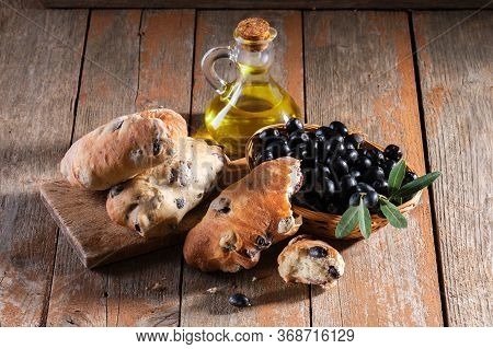 Traditional Italian Puccia Breads With Black Olives On A Cutten Board With Olive Oil And Fresh Black