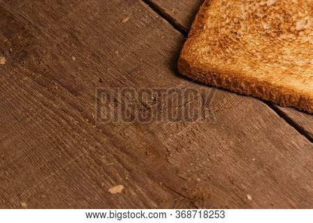 A Delicious Toasted Slice Of Toast Bread Lies On A Natural Brown Wooden Background.