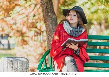 Girl Inspired By Nature Sits On The Bench In Park Writing A Poem Or Song In A Notebook.