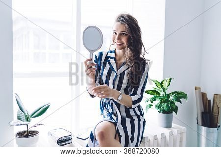 Dressy Cheerful Woman Looking At Glass And Preparing For Date