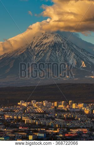 Evening View From Above Of Cityscape Petropavlovsk-kamchatsky At Sunset On Background Active Volcano
