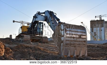 Excavator Working At Construction Site On Road Work. Backhoe Digs Ground For The Foundation And For