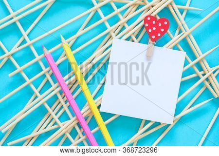 Notepaper Holding By Clothes Pin With Heart, Pencils On A Abstract Blue Background. Colorful Pencils
