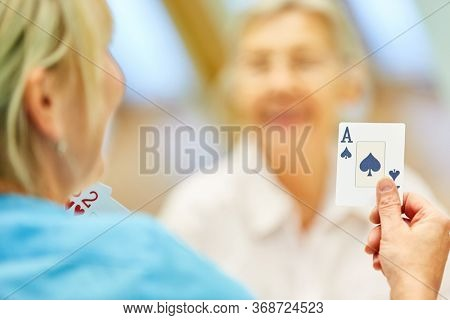 Nursing Woman plays cards with senior citizens in assisted living or at home