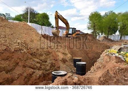 Excavator On Earthwork During The Laying Of Pipes Of The Heating System To A New Residential Buildin