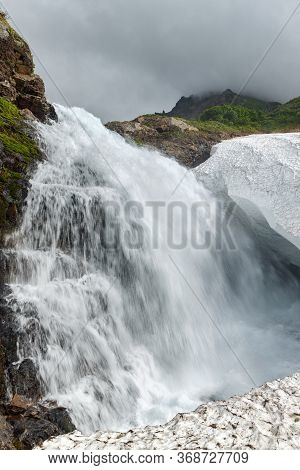 Scenery View Of Idyllic Cascade Waterfall Falling Into Snowfield In Rocky Mount