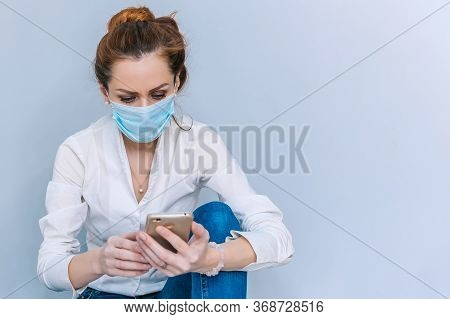 Girl With A Medical Mask Speaks On The Phone Sitting On The Floor. Concept On The Theme Of Coronavir