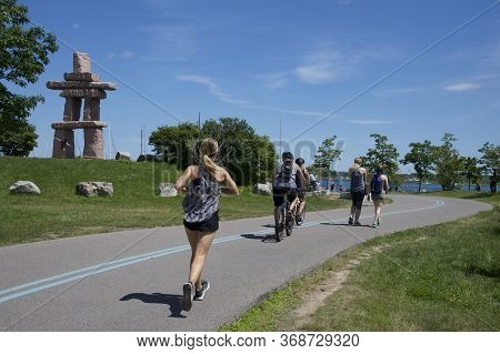Toronto, Ontario / Canada - 03/07/2017: Jogging In The Park Near Lake Ontario On A Sunny Summer Day