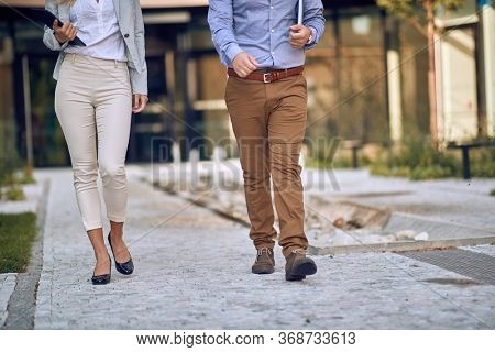 cropped image of male and female businesspeople walking through arranged park