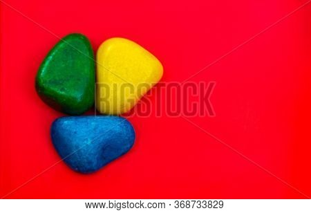Multi Color Natural Pebbles Green, Blue And Yellow Stone Isolated On Red Background With Space For C