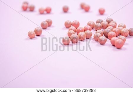 Balls Of Blush Scattered On A Table On A Pink Background