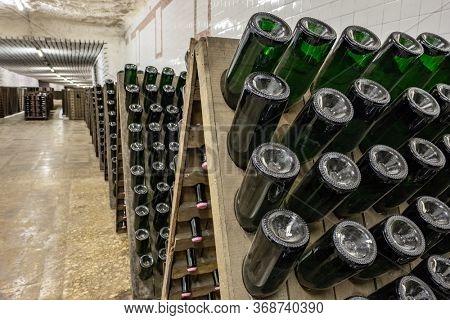 Sparkling wine bottles stacked up in old wine cellar close-up background. Underground wine cellars in Moldova