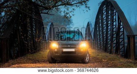 Perechin, Ukraine - Oct 20, 2019: Suv Headlights In Foggy Darkness. Car On The Old Metal Bridge With