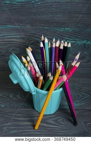 Pencil Filled With Colored Pencils. In The Form Of A Garbage Container. Near A Few Pencils. Against