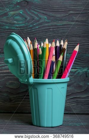 Pencil Filled With Colored Pencils. In The Form Of A Garbage Container. Against The Background Of Br