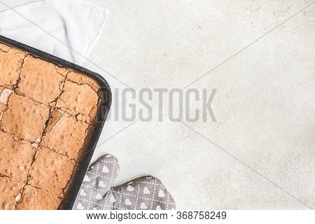 Top View Of Freshly Baked Home Made Brownie Cake Cut In Squares Over White Rustic Background. Copy S