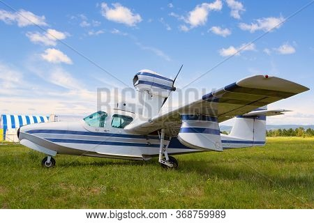 Light Private Plane Parked On The Grassy Airfield