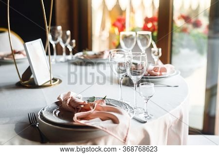 Close Up Festive Table Setting With Empty Wine Glasses And Plate