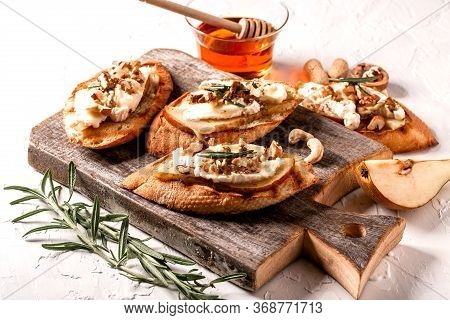 Bruschettas With Brie Camembert Cheese, Pear, Nuts And Honey With Sprigs Of Rosemary On A Light Tabl