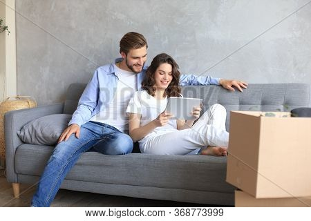 Happy Couple Sitting And Planning New Home Decoration At Home With A Tablet At Moving Day, Renovatio